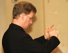 Close up of Andrew, baton in hand, conducting